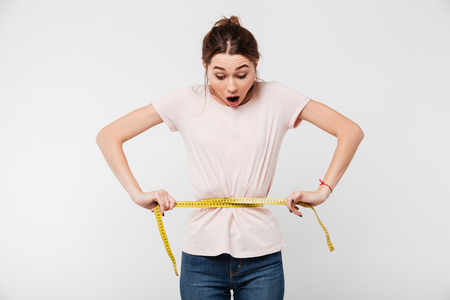 Foto de Portrait of a slim astonished woman holding measuring tape around her waist isolated over white background - Imagen libre de derechos