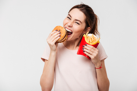Photo pour Close up portrait of a happy pretty girl eating french fries and a burger isolated over white background - image libre de droit