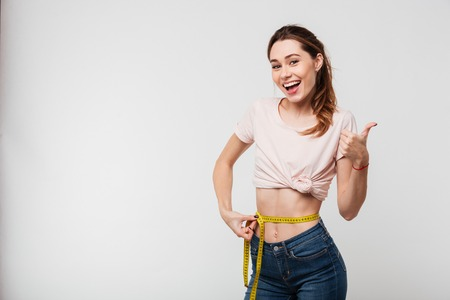 Foto de Portrait of a slim satisfied woman holding measuring tape around her waist and showing thumbs up isolated over white background - Imagen libre de derechos
