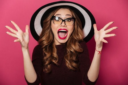 Picture of young shocked lady wearing hat and glasses standing isolated over pink background. Looking camera.