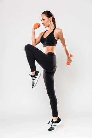 Foto de Full length portrait of a healthy young asian fitness woman doing exercises with dumbbells isolated over white background - Imagen libre de derechos