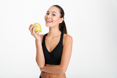 Photo pour Portrait of a smiling asian fitness woman holding apple isolated over white background - image libre de droit
