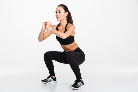Foto de Portrait of a confident asian fitness woman doing squats isolated over white background - Imagen libre de derechos