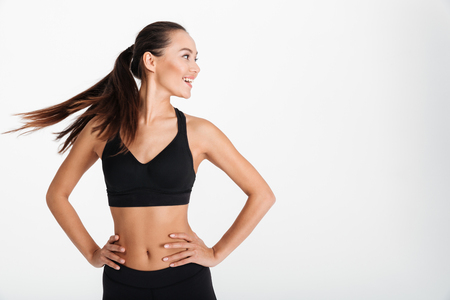 Foto de Portrait of a smiling asian fitness girl standing with arms on hips and looking away isolated over white background - Imagen libre de derechos