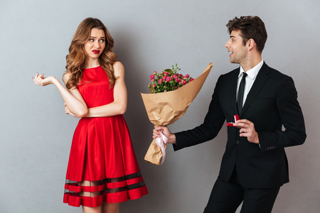 Foto de Portrait of a happy man proposing to a unsatisfied girl with flowers and an engagement ring over gray wall background - Imagen libre de derechos