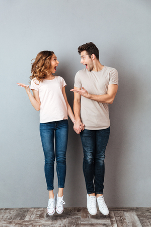 Photo pour Full length portrait of a happy young couple holding hands and jumping over gray wall - image libre de droit