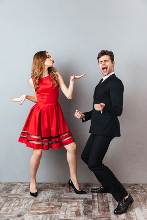 Photo pour Full length portrait of a happy cheery couple dressed in formal wear dancing together and having fun over gray wall background - image libre de droit