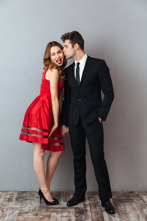 Full length portrait of a happy smiling couple dressed in formal wear kissing while holding hands over gray wall background