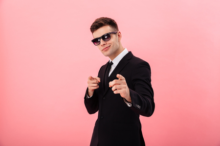 Foto de Confident businessman in sunglasses pointing at camera while standing isolated over pink - Imagen libre de derechos