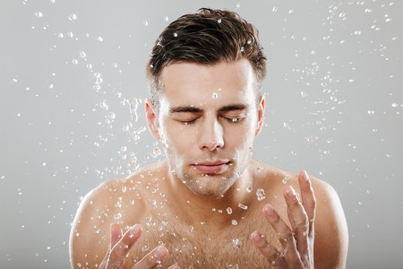 Close up portrait of a young half naked man surrounded by water drops washing his face isolated over gray background