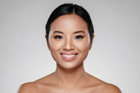 Foto de Beauty portrait of a beautiful half asian woman looking at camera isolated over gray background - Imagen libre de derechos