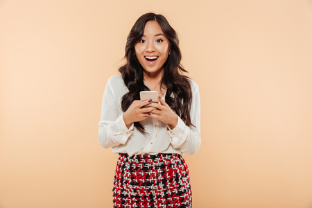 Photo for Portrait of an excited asian woman standing and using mobile phone isolated over beige background - Royalty Free Image