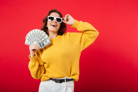 Photo pour Portrait of a happy woman in sunglasses posing while holding bunch of money banknotes isolated over pink background - image libre de droit