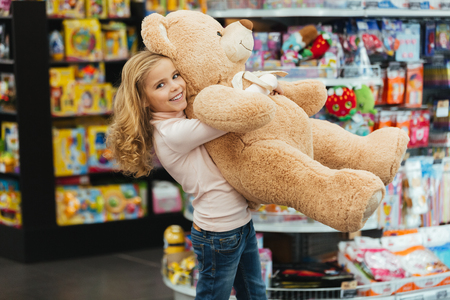 Photo pour Smiling little girl holding big teddy bear while standing at the supermarket - image libre de droit