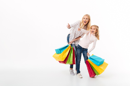 Photo pour Full length portrait of a shocked mother and her little daughter standing with shopping bags and pointing fingers away isolated over white background - image libre de droit