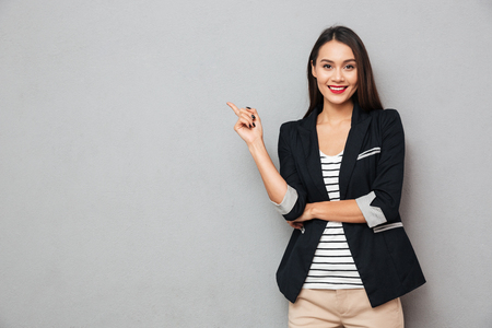 Foto de Smiling asian business woman pointing up and looking at the camera over gray background - Imagen libre de derechos
