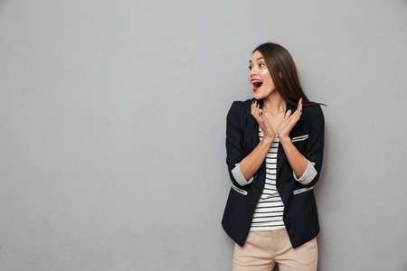 Photo pour Surprised happy asian business woman screaming and looking away over gray background - image libre de droit