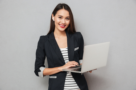 Photo pour Happy asian business woman holding laptop computer and looking at the camera over gray background - image libre de droit