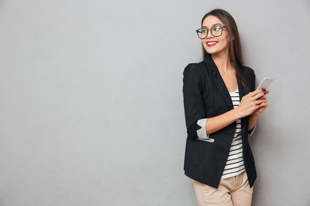 Foto de Smiling asian business woman in eyeglasses holding smartphone and looking back over gray background - Imagen libre de derechos