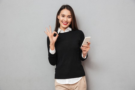 Foto de Pleased asian woman in business clothes holding smartphone and showing ok sign while looking at the camera over gray background - Imagen libre de derechos