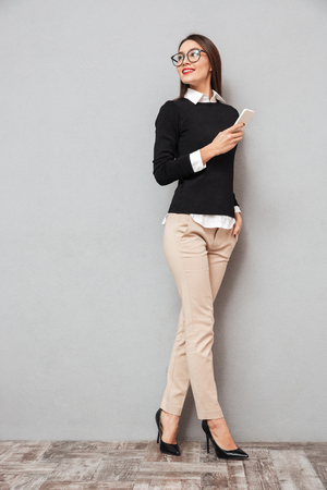 Photo pour Full length image of Smiling asian woman in business clothes and eyeglasses holding smartphone while looking back over gray background - image libre de droit