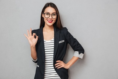 Foto de Smiling asian business woman in eyeglasses with arm on hip showing ok sign and looking at the camera over gray background - Imagen libre de derechos