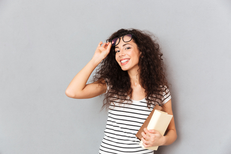 Photo pour Young female teacher in eyeglasses with curly hair standing with books in hand over grey wall enjoying her work in college, being clever and intellectual - image libre de droit