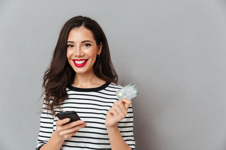 Portrait of a happy girl holding mobile phone and a credit card isolated over gray background