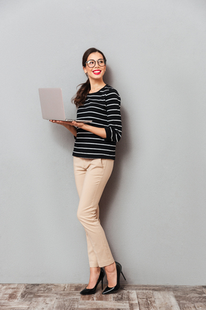 Foto de Full length portrait of a happy woman in eyeglasses holding laptop computer and looking away at copy space isolated over gray background - Imagen libre de derechos