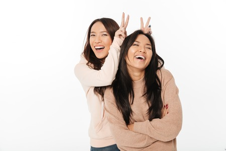 Foto de Picture of two asian cute ladies sisters standing isolated over white background looking camera have fun. - Imagen libre de derechos