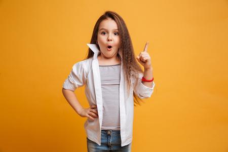 Photo pour Image of surprised little girl child standing isolated over yellow background have an idea. - image libre de droit