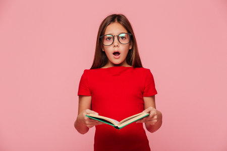 Photo pour Surprised brunette girl nerd in eyeglasses looking camera with opened mouth while reading book isolated - image libre de droit