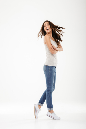 Full length image of Cheerful brunette woman posing sideways and looking back over gray backgroundの写真素材
