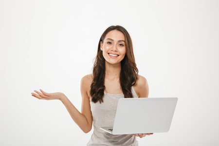 Image of amazing businesswoman holding silver laptop and gesturing with smile over white wall