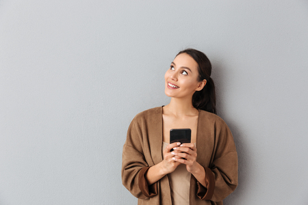 Photo for Portrait of a happy young asian woman holding mobile phone while standing and looking away over gray background - Royalty Free Image