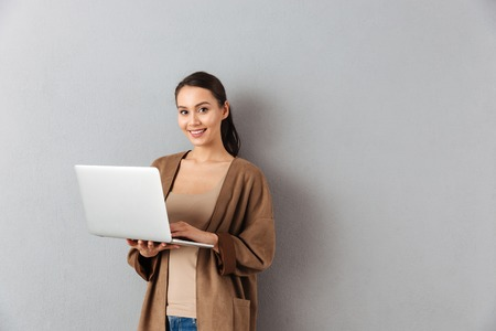 Photo for Portrait of a happy young asian woman holding laptop computer while standing and looking at camera over gray background - Royalty Free Image