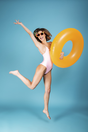 Foto de Full length portrait of a cheerful girl dressed in swimsuit and sunglasses holding inflatable ring and jumping isolated over blue background - Imagen libre de derechos