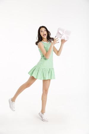 Foto de Full length portrait of a joyful girl dressed in dress standing and holding gift box isolated over white background - Imagen libre de derechos