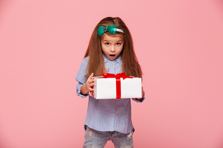 Cute girl 5-6 years holding present box with open mouth, being excited and surprised to get birthday gift over pink background