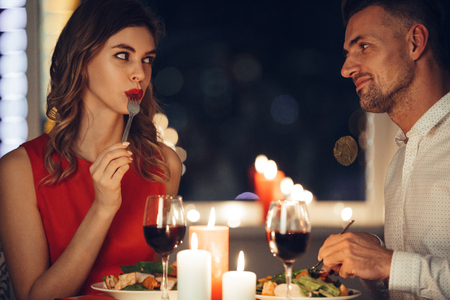 Photo for Young beautiful woman in red dress eating and flirting with her man while have romantic dinner in the evening - Royalty Free Image