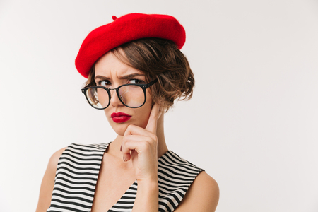 Foto de Portrait of a disappointed woman wearing red beret and eyeglasses looking at camera isolated over white background - Imagen libre de derechos