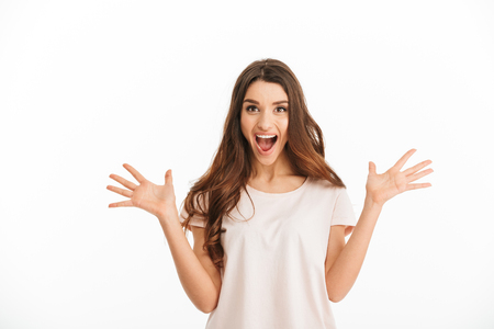 Photo for Surprised happy brunette woman in t-shirt screaming and looking at the camera over white background - Royalty Free Image