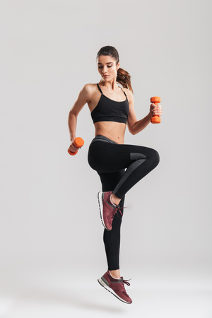 Foto de Full-length photo of sporty woman workout with small dumbbells isolated over gray background - Imagen libre de derechos