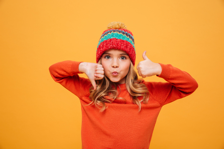 Photo pour Funny Young girl in sweater and hat showing thumb up and down while looking at the camera over yellow background - image libre de droit