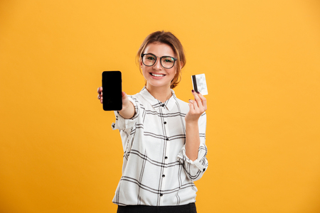Foto de Portrait of cheerful woman wearing eyeglasses holding smartphone and credit card in hands isolated over yellow background - Imagen libre de derechos