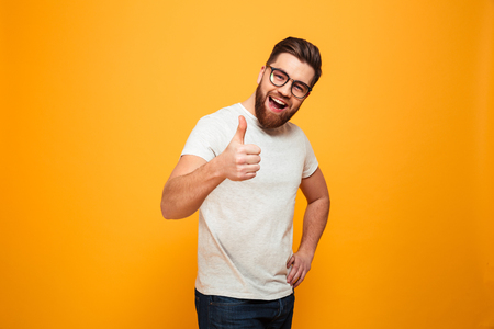 Foto de Portrait of a confident bearded man in eyeglasses showing thumbs up isolated over yellow background - Imagen libre de derechos