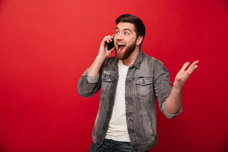 Foto de Photo of handsome excited man expressing surprise on face and gesturing while speaking on telephone isolated over red background - Imagen libre de derechos