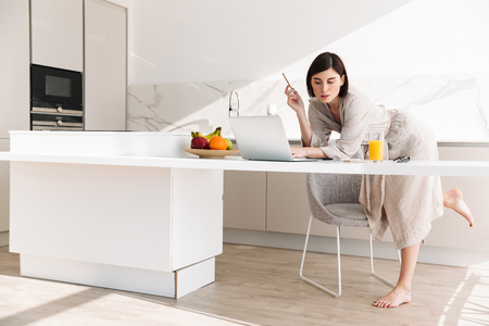 Foto de Smart concentrated woman in housecoat sitting at table in kitchen and working on laptop while having breakfast - Imagen libre de derechos