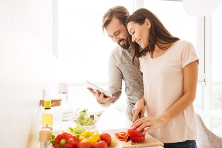 Photo pour Portrait of a cheerful young couple cooking salad together according to a recipe on a tablet computer - image libre de droit