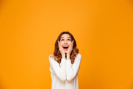 Foto de Surprised happy brunette woman in sweater holding her cheeks and looking up over yellow background - Imagen libre de derechos